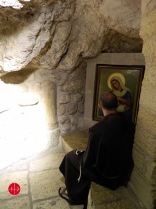 (Holy Land) Palestine, Bethlehem 01.12.2012 A Franciscan friar praying in front of an icon in the milk grotto in Bethlehem. The place - close to nativity church - is dear to Christians and Muslims because the virgin Mary is said to have lost her