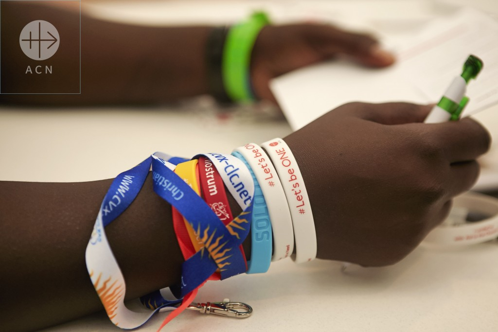"Poland, Krakow 27.07.2016 The ACN (Aid to the Church in Need) stand at the Vocational Centre: The young participant is wearing different WYD bracelets - among the also the one of ACN with ""Let´s Be One"""